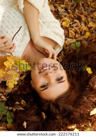 brunette woman lying on autumn leaves, outdoor portrait