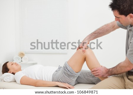 Brunette woman lying while a physiotherapist manipulates her leg indoors