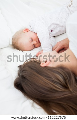 Brunette woman lying with her baby on her bed indoors