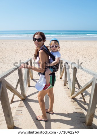 brunette woman mother carrying in backpack rucksack her two year blonde baby old with blue hat white sunglasses walking at a beach in Cadiz Spain - stock photo