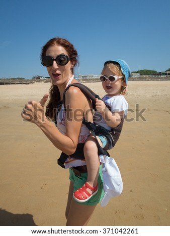 brunette woman mother carrying in backpack rucksack her two year blonde baby old with blue hat white sunglasses with thumb up fingers singing happy at a beach in Cadiz Spain - stock photo