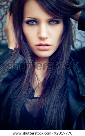 brunette woman near cracked wall. Specially toned fashion photo - stock photo