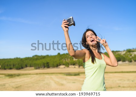 Brunette woman on summer vacation trip taking selfie photo with retro camera and having fun. Female traveler enjoying countryside in Spain. - stock photo