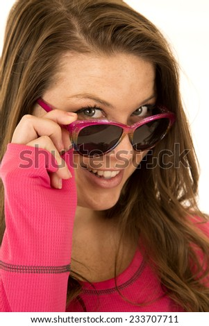 Brunette woman peering over sun glasses smiling