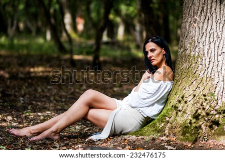 Brunette woman posing in the forest with beautiful light  - stock photo