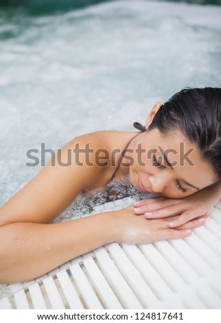 Brunette woman resting at edge of jacuzzi - stock photo
