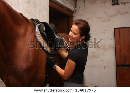 Brunette woman saddling up brown horse in the stables - stock photo