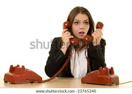 Brunette woman secretary sitting at desk with two red retro rotary telephone hand sets on ears looking overwhelmed - stock photo