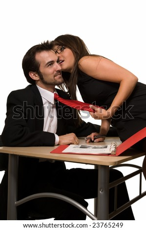 Brunette woman sitting on a desk in front of laptop computer with a man coworker whispering in his ear - stock photo