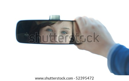 Brunette woman sitting on driver's seat and looking in the rear-view mirror - stock photo