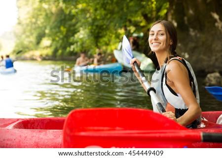 Brunette woman smiling in a canoe doing kayaking
