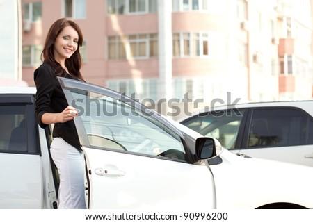 brunette woman standing near her white car - stock photo