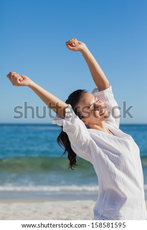 Brunette woman stretching at beach on a sunny day - stock photo