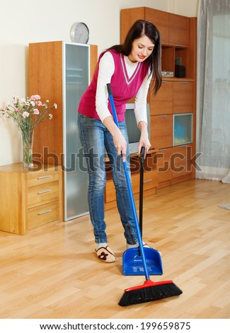 Brunette  woman sweeping the floor at home - stock photo