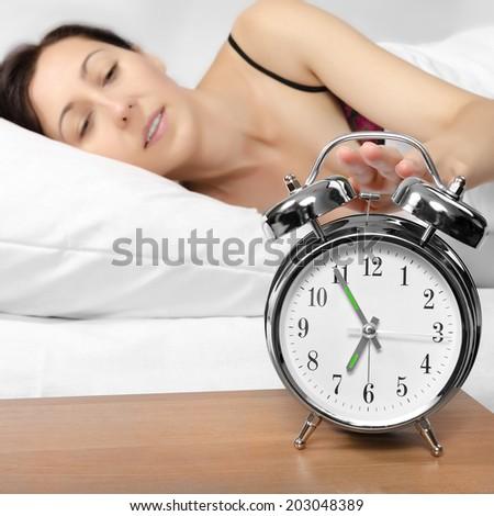 Brunette woman turning off her alarm clock in her bedroom - stock photo