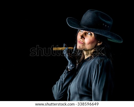 Brunette woman wearing a black dress, gloves, and cowboy hat standing in front of a dark backdrop, holding a cigar between her fingers and looking upwards with a playful expression on her face. - stock photo
