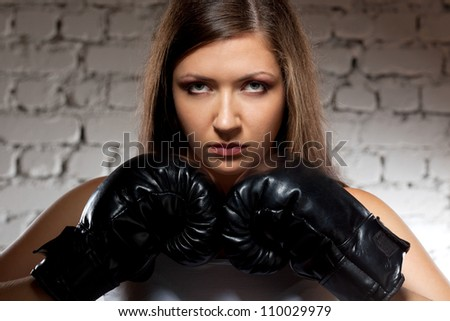 brunette woman wearing boxer gloves over brick wall with