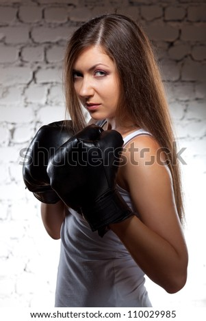 brunette woman wearing boxer gloves over brick wall with flying hair - stock photo