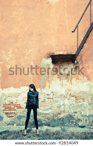 brunette woman wearing leather jacket on ruins near stairway