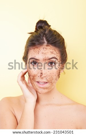 Brunette woman with a scrub applied on her face - stock photo