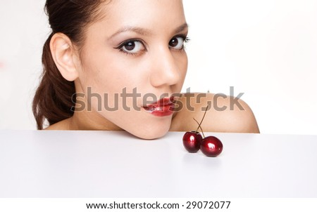 brunette woman with brown eyes next to two cherries - stock photo