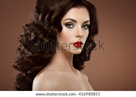 Brunette woman with curly hairstyle. Beautiful girl with long wavy hair. Perfect makeup. Fashion photo - stock photo