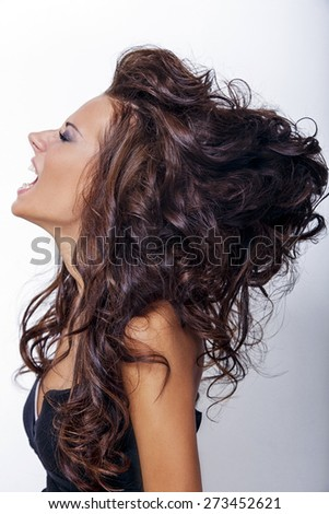 Brunette woman with hairstyle in black dress on white background