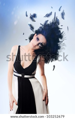 brunette woman with magnificent hairstyle of black feathers and art make up - stock photo