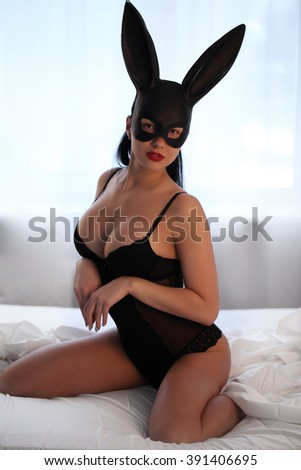 brunette woman with sexy lingerie and fluffy bunny ears studio - stock photo