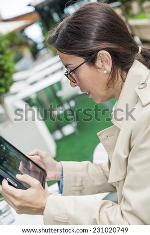 Brunette woman working outside with phone and tablet, drinking coffee