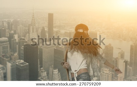 Brunette women with skateboard in her hands on New York City background. Sexy nice woman in jeans hold longboard in her hands in summer evening weather urban style street fashion hipster trendy photo. - stock photo