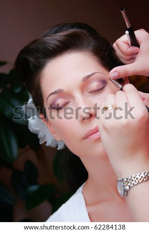 brunette young bride prepare for the event by makeup artist - stock photo
