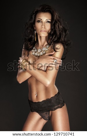 Brunette young lady with long curly hair posing in black panties. A lot of jewellery.