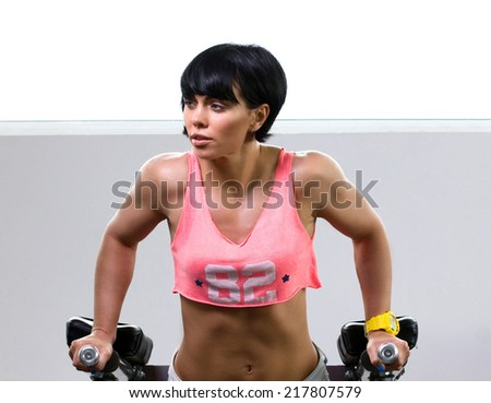brunette young woman doing athletic exer?i?e on light wall background  - stock photo