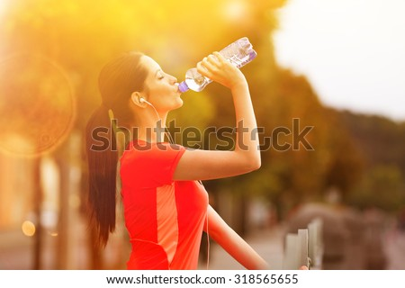 Brunette young woman runner drinking bottle of water.  - stock photo