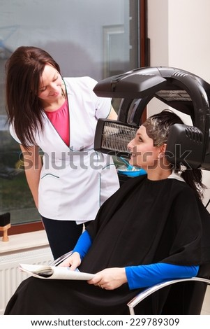 Brunette young woman with newspaper in hairdressing beauty salon. Girl dying colouring hair by hairstylist. Hairdresser talking with client. Modern professional equipment. - stock photo