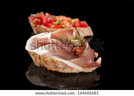 Bruschetta and prosciutto canape isolated on black. Culinary appetizer background. - stock photo