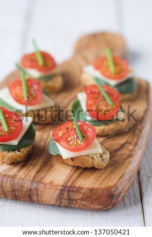 Bruschetta biscuits with tomato, spinach & cheese & a chive garnish - shallow dof - stock photo