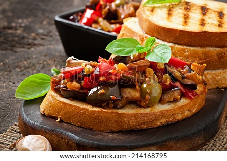 Bruschetta caponata with raisins and pine nuts decorated with a leaf of basil - stock photo
