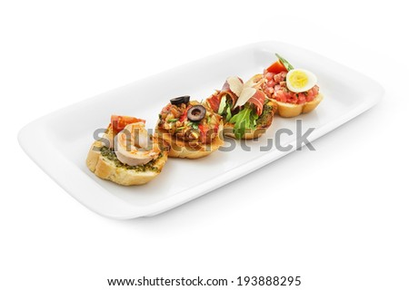 Bruschetta collection with tiger prawns, tuna pate & quail egg, Parmesan cheese & Pesto sauce, prosciutto & arugula. Isolated on white background - stock photo