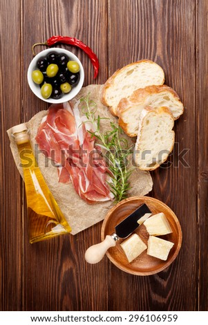 Bruschetta ingredients - prosciutto, olives, cheese. Top view on wooden table