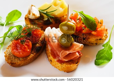 Bruschetta, italian toasted bread with prosciutto, olives, tomato and cheese - stock photo