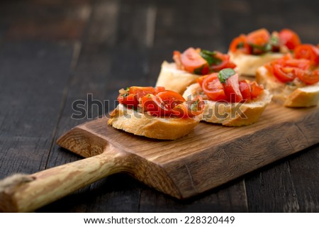 bruschetta set on vintage wooden board - stock photo