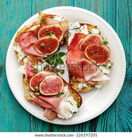 Bruschetta with blue cheese, smoked ham and fresh figs - stock photo