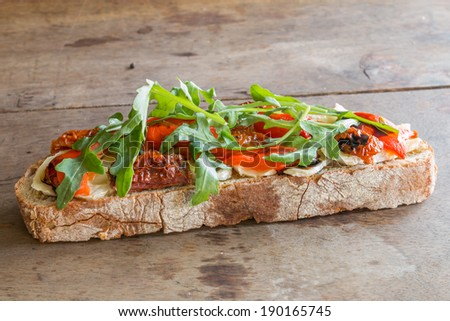 bruschetta with brie and arugula on wooden surfaces