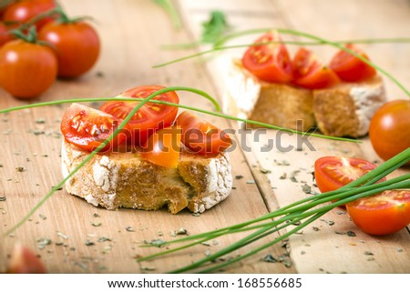 Bruschetta with cherry tomato and chive on Wooden table - stock photo
