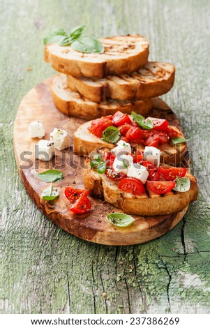 Bruschetta with chopped tomatoes, basil and cheese on grilled crusty bread - stock photo