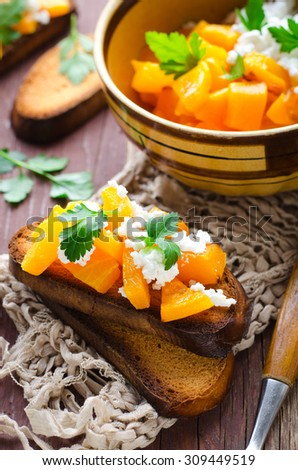 Bruschetta with chunks of pumpkin, goat cheese and parsley. selective focus - stock photo