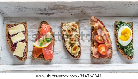 Bruschetta with different toppings on the wooden tray - stock photo