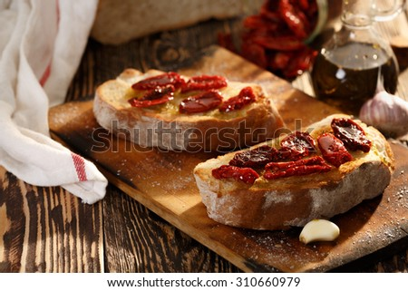Bruschetta with dried tomatoes, garlic and olive oil. Traditional Italian cuisine sandwich made of grilled ciabatta. Antipasti